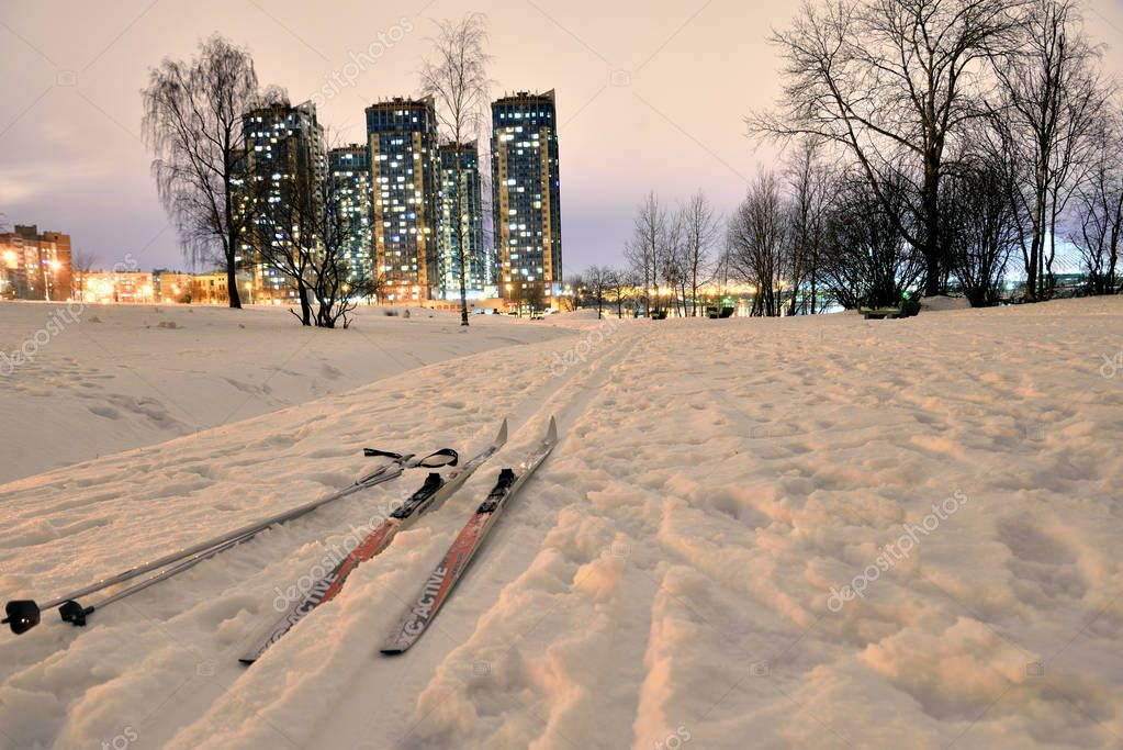Cross-country skiing in park at winter night.