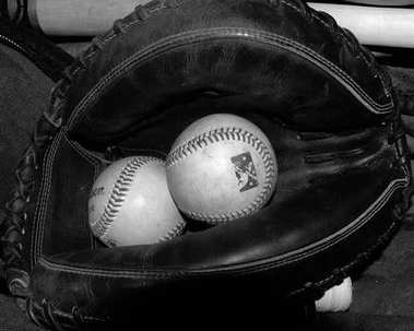 Baseball glove and Baseball sitting on the bench in the dugout before a game.