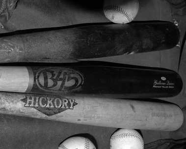 Baseball bats sitting in the dugout for a baseball to use.