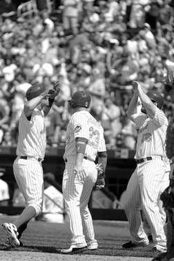 Baseball Players celebrate at home plate after getting a big hit.