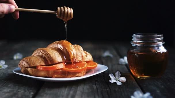 Čerstvý croissant s pomerančem a sklenice medu na kuchyňském stole.