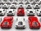 Photo Three red sports cars stand out amongs many white cars
