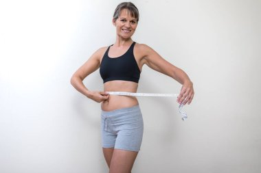 Middle aged woman with a tape measure.