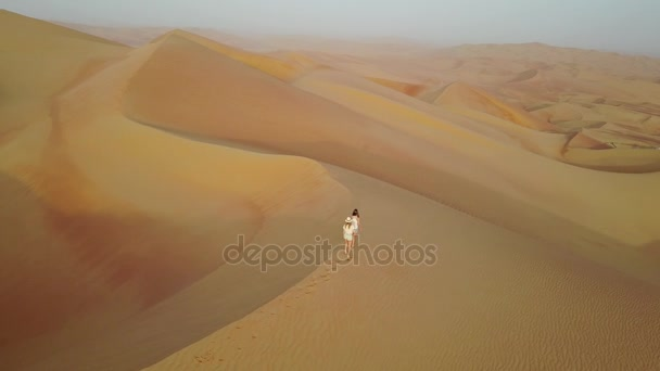 Dvě ženy chodit na písečné duně během východu slunce při pohledu z sondu.