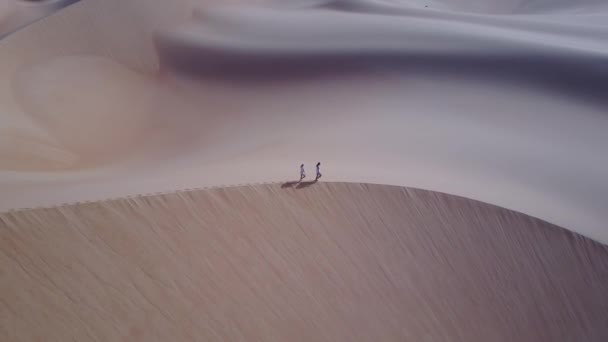 Two women walking on a sand dune during sunrise as viewed from a drone.