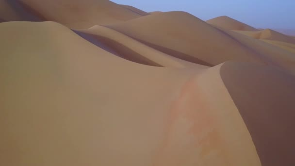 Drone view of sand dunes at sunrise.