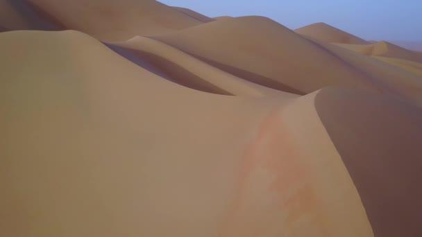 Drohnenblick auf Sanddünen bei Sonnenaufgang.