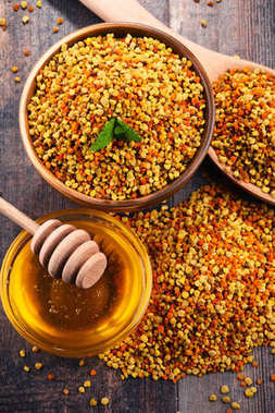 Bowls with bee pollen and honey on kitchen table