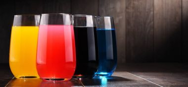 Glasses of assorted carbonated soft drinks