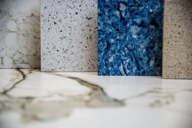 quartz stone kitchen counter top color samples on a white carrara marble worktop surface