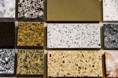 Samples of natural stone in different sizes used as a kitchen counter tops. Granite, quartz and marble countertops