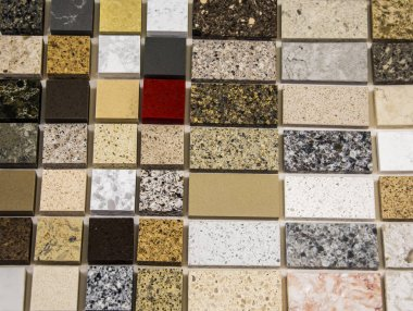 Colorful samples of natural stone in different sizes used as a kitchen counter tops. Granite, quartz and marble countertops