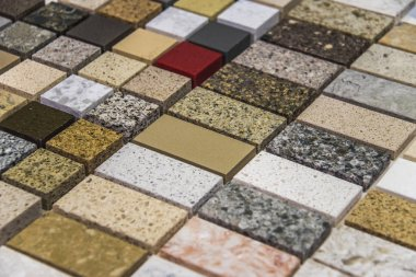 Colorful square natural stone samples used as a kitchen counter top. Granite and marble countertops