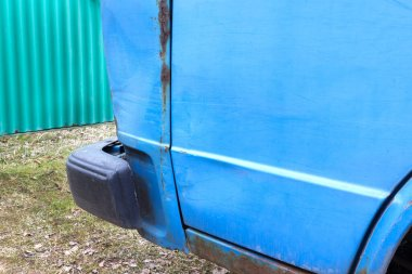The old battered car is blue, with traces of rust and damage. It is dangerous for drivers on the road.