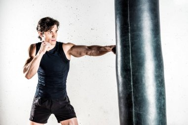 Muscular male kickboxer in sportswear boxing in punching bag stock vector