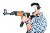 Fotografia uomo in cuffie da realtà virtuale con il fucile