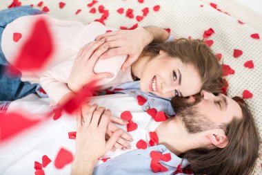 Beautiful couple in love lying on red paper hearts and kissing stock vector