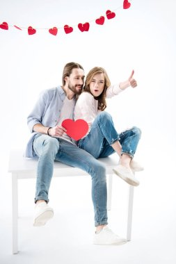 Young happy couple in love holding red paper heart and sitting on table, man shows thumb up isolated on white stock vector