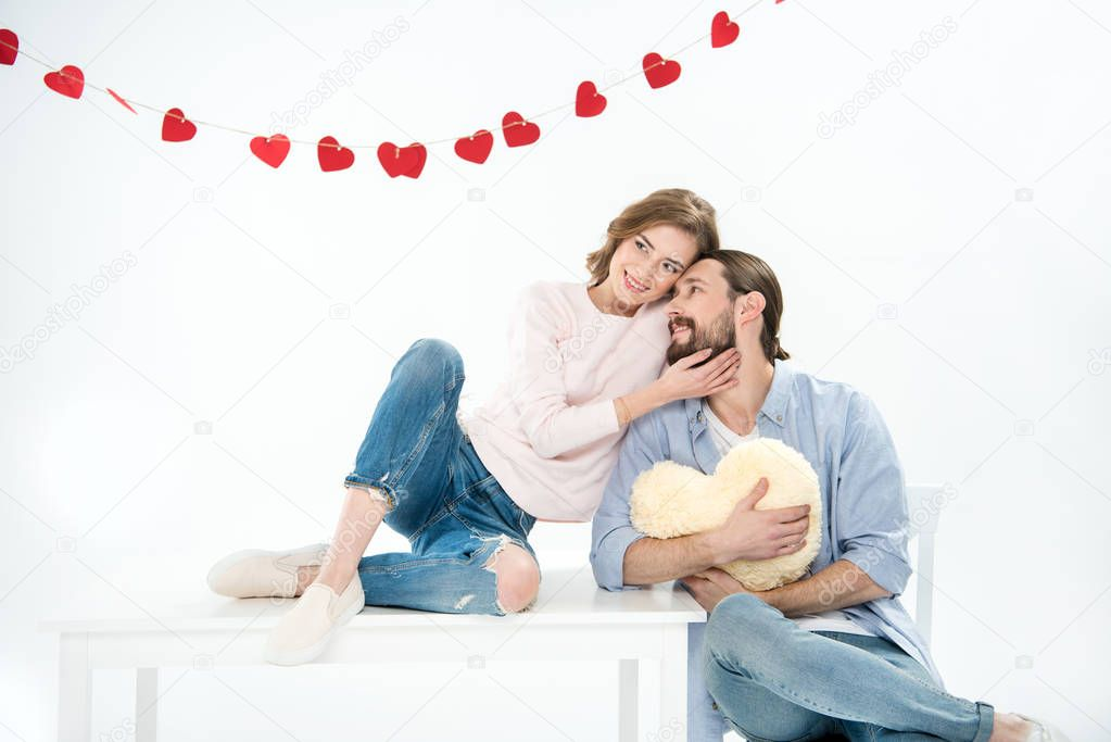Beautiful young couple in love sitting on white furniture with heart shaped pillow isolated on white stock vector