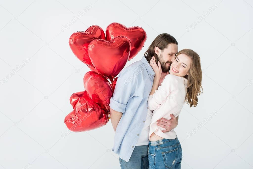 Young couple holding heart shaped air balloons and embracing isolated on white stock vector