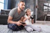 Otec a dcera hraje s joysticky