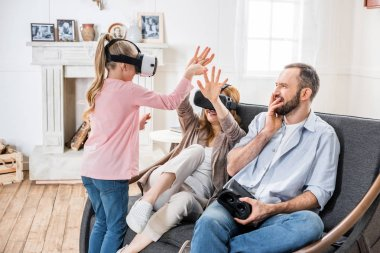 Family in virtual reality headsets