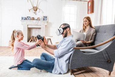Young family of three having fun using virtual reality headset and laptop stock vector