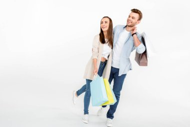 Happy young couple with shopping bags embracing and looking away  isolated on grey stock vector
