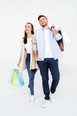 Full length view of happy young couple walking with shopping bags  isolated on white stock vector