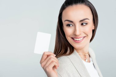 Portrait of smiling woman looking at credit card in hand isolated on grey stock vector