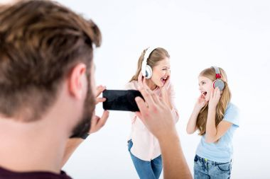 father taking photo of mother and daughter