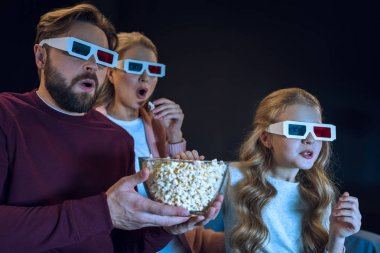 Shocked family in 3d glasses watching movie and eating popcorn   isolated on black stock vector