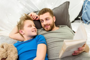 Father and son reading book