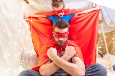 Father and son in superhero costumes