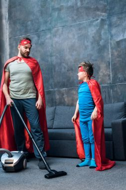 father and son in superhero costumes vacuuming