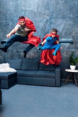 Father and son in superhero costumes jumping on sofa at home stock vector