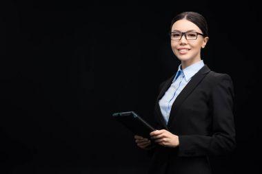 Brunette businesswoman in black suit using digital tablet isolated on black stock vector