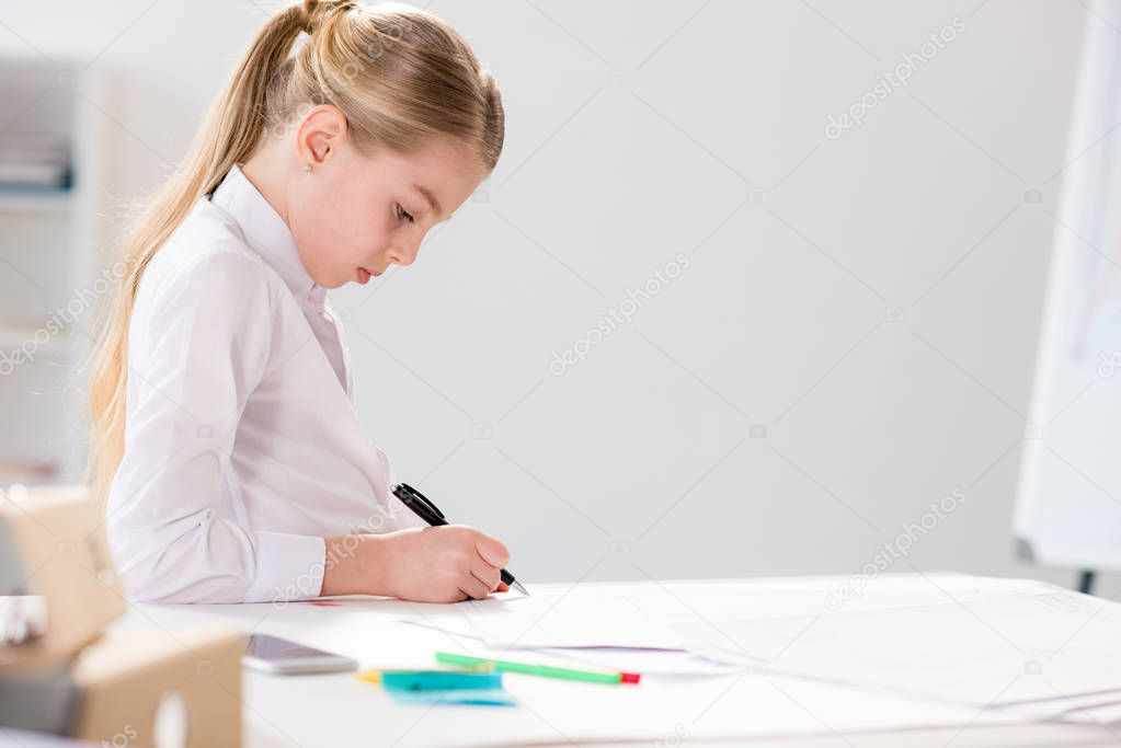 serious little girl writing at table