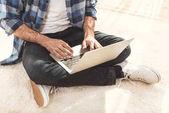 Muž sedí na koberci a psaní na notebooku