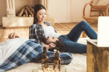 couple lying together on carpet and talking