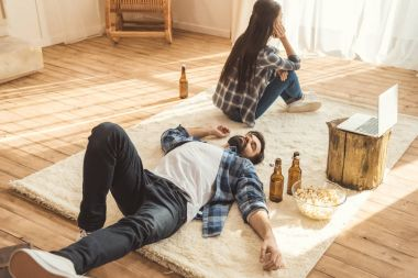woman sitting on floor near drunk boyfriend