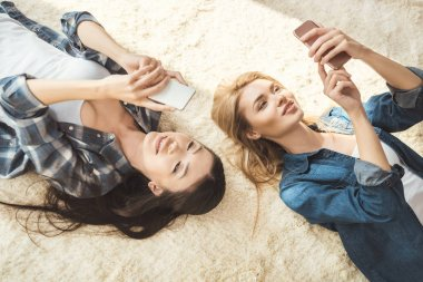 Overhead view of two women taking selfie while lying on floor stock vector