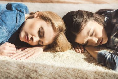 women sleeping on carpet