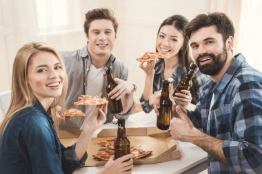 couples drinking beer and eating pizza