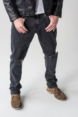 man posing in ripped jeans