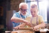 Großvater und Enkelin machen Teig