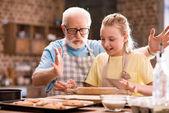 Großvater und Enkelin kneten Teig