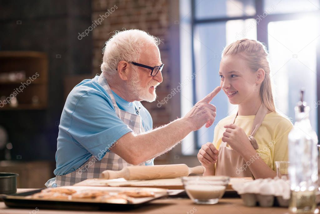 grandfather and granddaughter kneading dough