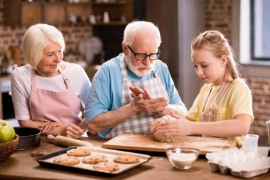 Grandmother, grandfather and granddaughter cooking and kneading dough for cookies at kitchen table, cooking in kitchen concept stock vector
