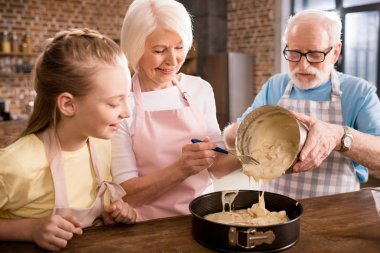 grandparents and girl cooking together